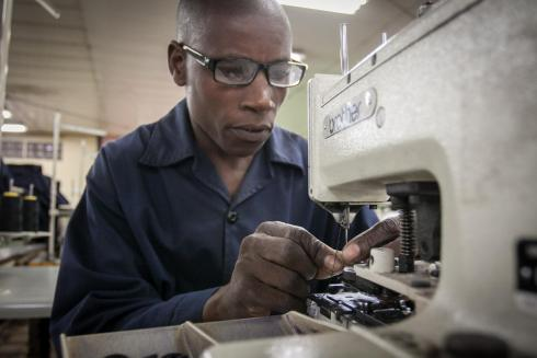 Man sewing in reading glasses